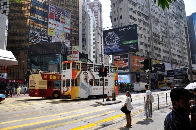 A double-decker streetcar next to an open top double-decker bus on Hong Kong Island.